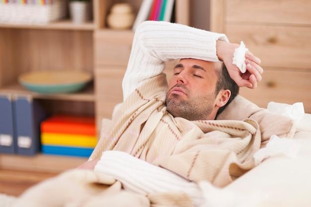 Больной человек, лежа на диване с высокой температурой Бесплатные Фотографии