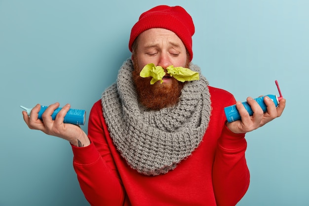Sick man in warm clothes with paper tissues in nose  and spray for sore throat Free Photo