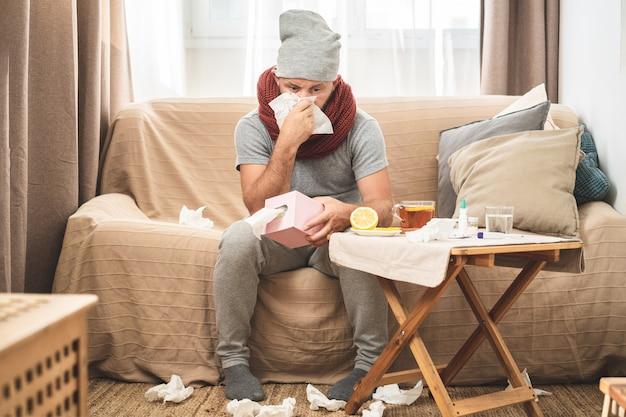 Больной человек в серой шапке и шарфе, сморкается и чихает в ткани. Premium Фотографии