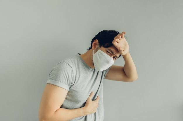 ウイルスの概念で灰色のtシャツに白い衛生マスクを身に着けている病人。 Premium写真