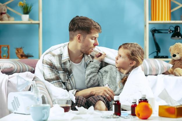 Uomo malato con la figlia a casa. trattamento domiciliare. combattere con una malattia. assistenza medica. insufficienza familiare. l'inverno, l'influenza, la salute, il dolore, la paternità, il concetto di relazione. relax a casa Foto Gratuite