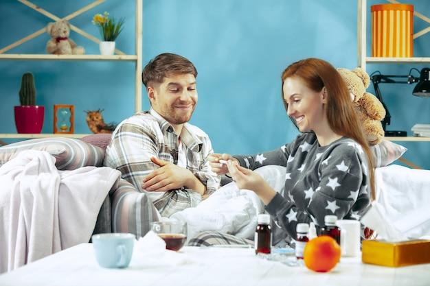Uomo malato con febbre sdraiata a letto con la temperatura. la sua moglie si prende cura di lui. la malattia, l'influenza, il dolore, il concetto di famiglia. relax a casa. concetti sanitari. Foto Gratuite