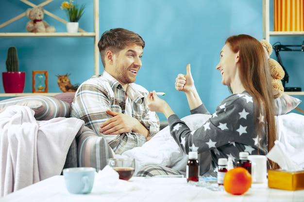 Uomo malato con febbre sdraiata a letto con la temperatura. la sua moglie si prende cura di lui. la malattia, l'influenza, il dolore, il concetto di famiglia. relax a casa Foto Gratuite