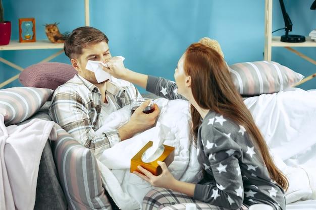 Uomo malato con febbre sdraiata a letto con la temperatura. la sua moglie si prende cura di lui. Foto Gratuite