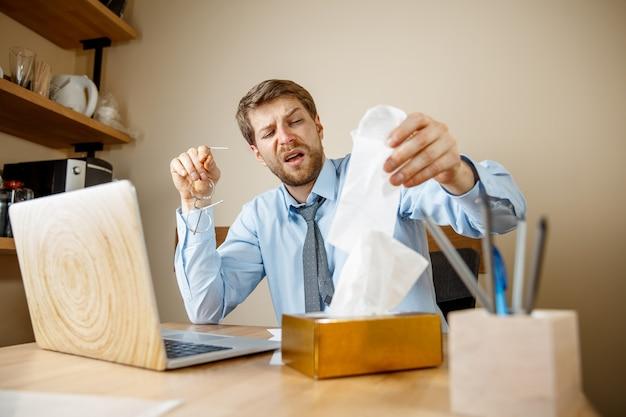 Uomo malato con il fazzoletto che starnutisce soffiando il naso mentre si lavora in ufficio, uomo d'affari preso freddo, influenza stagionale. influenza pandemica, prevenzione delle malattie, aria condizionata in ufficio causano la malattia Foto Gratuite