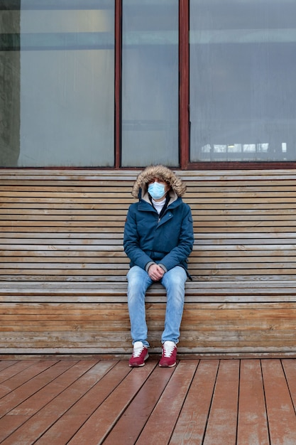 Premium Photo | Sick man with a hood sitting alone on bench, wearing  protective facial mask. coronavirus pandemic