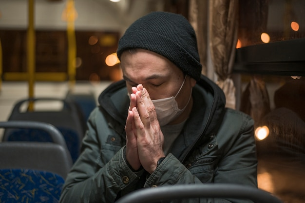 Sick man with medical mask praying in the bus Free Photo