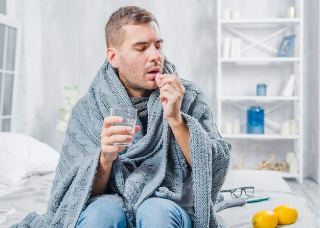Sick man wrapped in scarf sitting on bed taking pill with water Free Photo