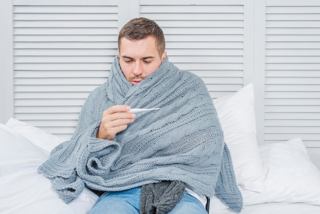 Sick man wrapped in shawl looking at thermometer Free Photo