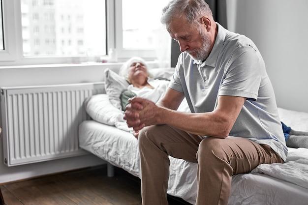 그녀, 지원 및 도움, 그녀 가까이 앉아 돌보는 노인 남편과 아픈 수석 여자, 남자는 머리를 아래로 앉는다. 의학 개념 프리미엄 사진
