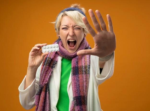 Больная нездоровая женщина с короткими волосами в теплом шарфе и шляпе, держащая блистер с таблетками, делает стоп-жест рукой, кричит, стоя на оранжевом фоне Бесплатные Фотографии