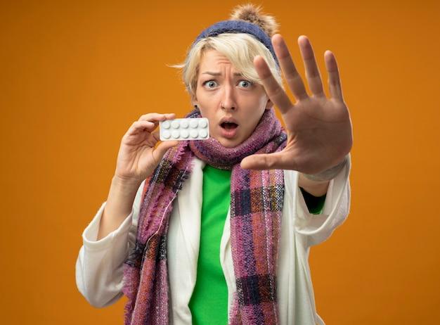 Больная нездоровая женщина с короткими волосами в теплом шарфе и шляпе, показывающая волдырь с таблетками, делая жест остановки с обеспокоенной и испуганной рукой, стоящей на оранжевом фоне Бесплатные Фотографии