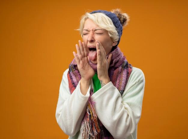 暖かいスカーフとオレンジ色の背景の上に立っている舌を突き出して咳が気分が悪いと短い髪の病気の不健康な女性 無料写真