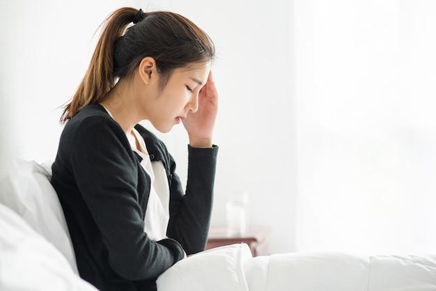 La donna malata aveva mal di testa e le mani le toccavano la testa sul letto. Foto Gratuite