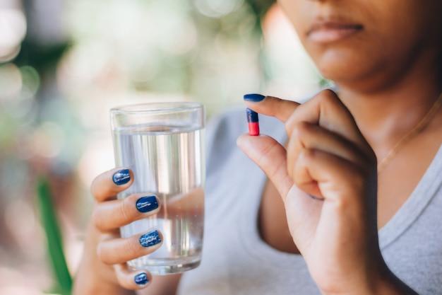 Больная женщина, держащая таблетки медицины и стакан воды. принимать лекарства. понятие личности и самолечения. оздоровительное лечение. депрессия, бессонница, боль Premium Фотографии