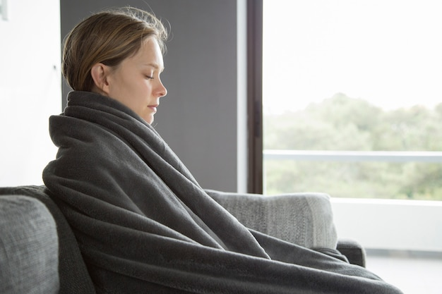 Sick woman keeping her eyes closed, meditating at home Free Photo