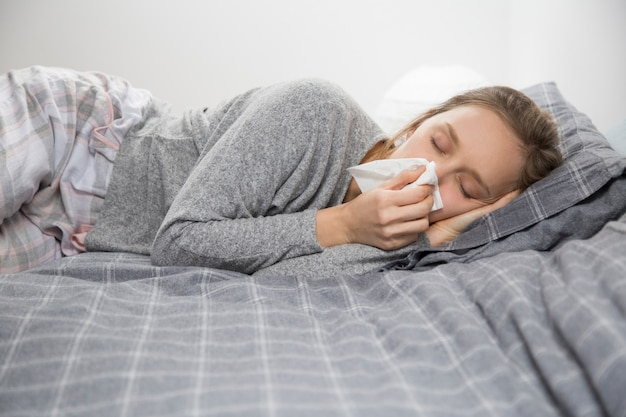 Sick woman lying in bed with closed eyes, blowing nose Free Photo