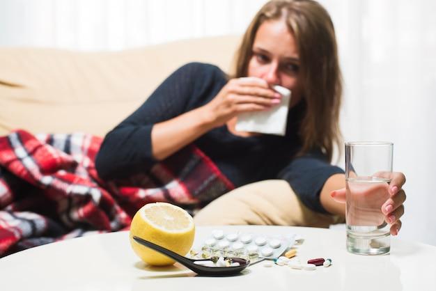 Больная женщина, лежа на диване под шерстяное одеяло чихая и вытирая нос. простудился Premium Фотографии