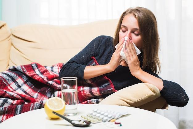 Больная женщина лежит на диване под шерстяным одеялом, чихая и вытирая нос Premium Фотографии
