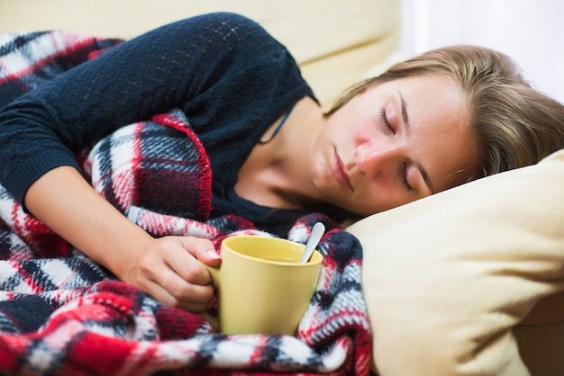 Sick woman lying on sofa under wool blanket with cup of tea Premium Photo