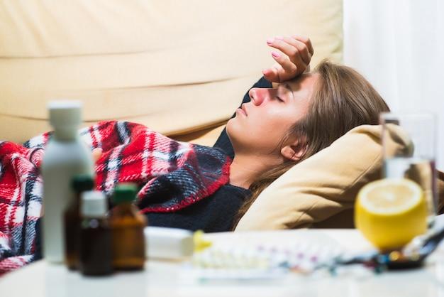Sick woman lying on sofa under wool blanket Premium Photo