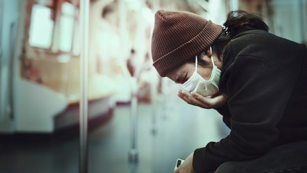 Donna malata con una maschera che tossisce in pubblico durante una pandemia di coronavirus Foto Gratuite
