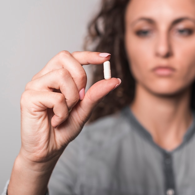 Sick woman showing white capsule in hand Free Photo