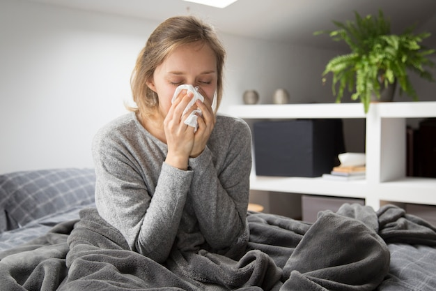 Sick woman sitting in bed, blowing nose with napkin Free Photo