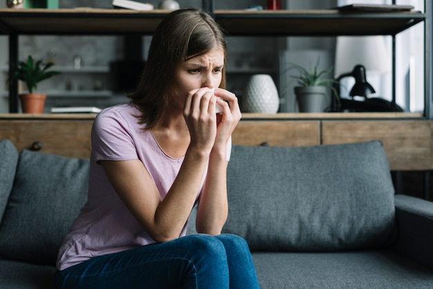 Sick woman sitting on sofa blowing nose with tissue paper Free Photo