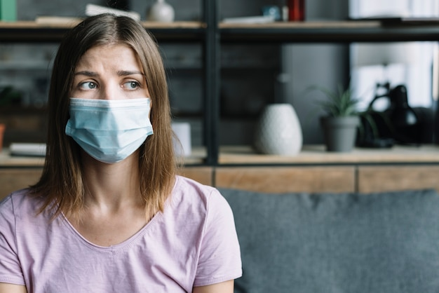 Sick woman wearing protective mask at home Free Photo