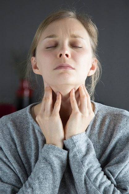 Sick woman with closed eyes having sore throat, touching neck Free Photo