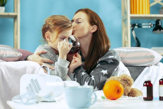 Больная женщина с дочерью дома. домашнее лечение. медицинское здравоохранение. Бесплатные Фотографии