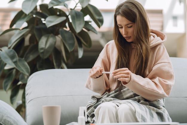 自宅で座っている頭痛と病気の女性 無料写真