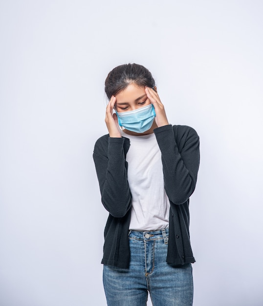 A sick woman with a headache wore a mask and placed a hand on her head. Free Photo