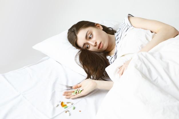 ベッドで朝を過ごし、彼女の手で丸薬の束を見て、白いシーツの上にこぼれた病気の若いブルネットの女性 無料写真