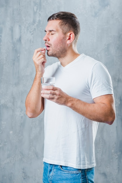 Sick young man standing against gray backdrop holding water glass in hand taking pill Free Photo