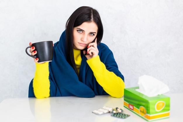 Больная молодая женщина покрыта одеялом, держа чашку чая, сидя за столом Бесплатные Фотографии