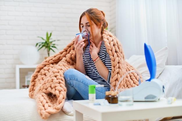 Больная молодая женщина устала от кашля, делает ингаляцию, используя небулайзер Premium Фотографии