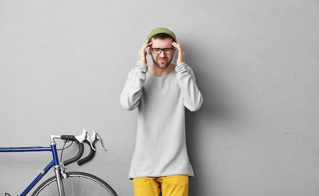 病気、片頭痛、不健康、健康上の問題。黄色のズボン、スウェットシャツ、緑の帽子、眼鏡をかけて、頭痛のためにこめかみを絞ったスタイリッシュなひげを剃っていない白人の男の写真 無料写真