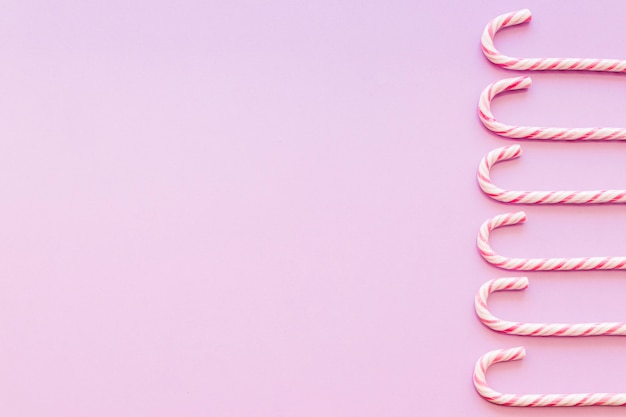 Side border made with christmas cane candies on pink background Free Photo