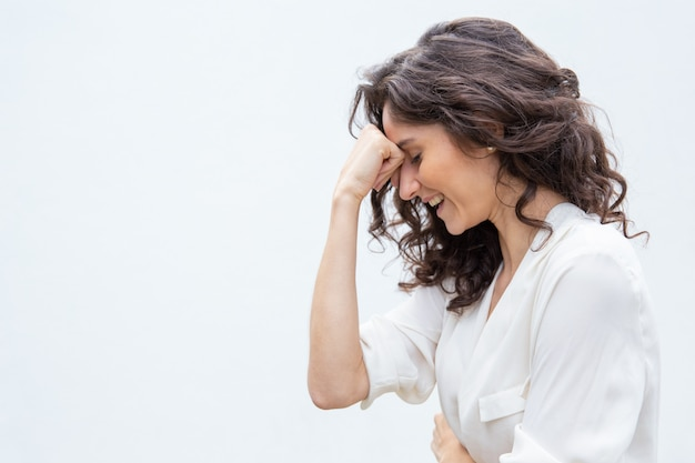 Side of cheerful woman with closed eyes leaning head on hand Free Photo