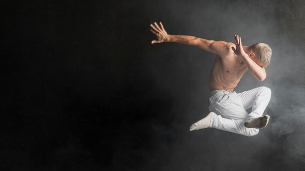 Side of male performer posing in mid-air in socks and jeans Free Photo