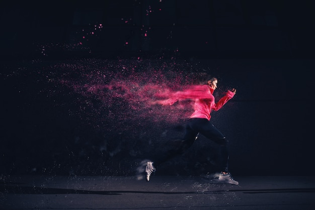 Side motion view of sexy fit athlete running girl in sportswear at the street in front of the grey wall. Premium Photo