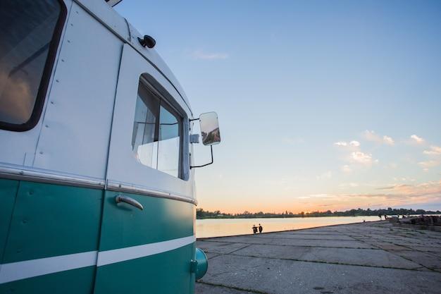 ビーチの近くに駐車した小さなバンの側 無料写真