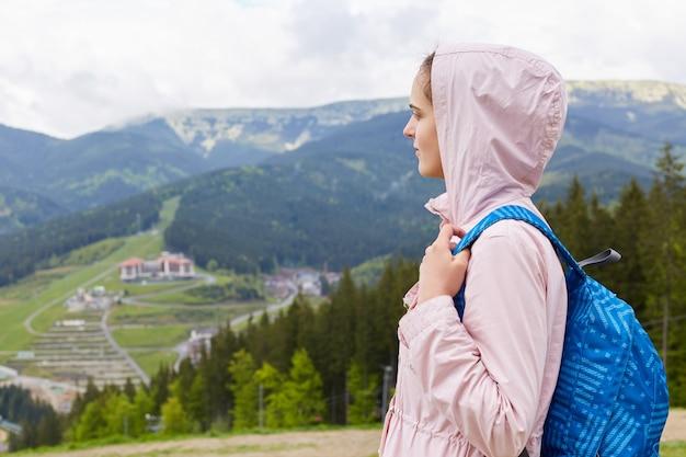 カジュアルなバラのジャケットと青いリュックサック、女性のバックパッキングと放浪を身に着けている魅力的な美しい少女の側面図 Premium写真