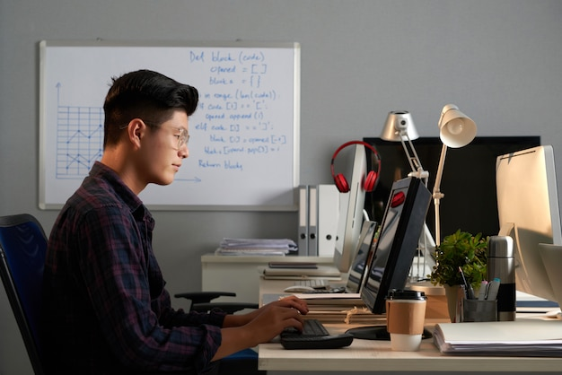 Side shot of young asian man in glasses working on computer in office Free Photo