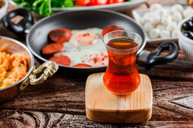 木製の表面においしい食事とお茶のカップの側面図 無料写真