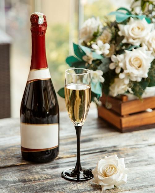 シャンパングラスとボトルと白いバラの側面図 無料写真