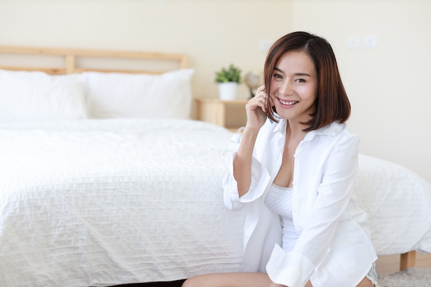 Side view of adult freelance asian woman in white shirt working on computer and cell phone in bedroom with happy smiling face Premium Photo