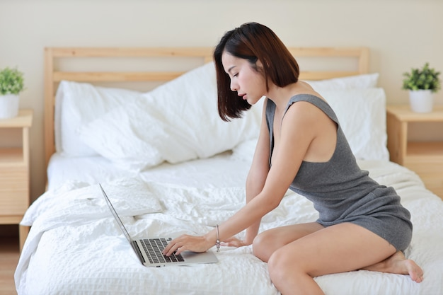 Side view of adult freelance asian woman working on computer and cell phone on bed in bedroom Premium Photo